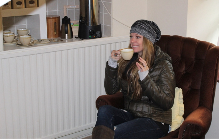 "alt=""woman drinking tea in brown chair"""